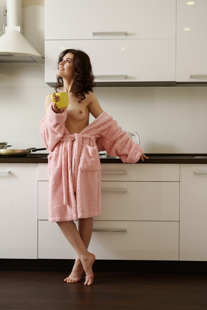 Erotica. Image of smiling woman posing in kitchen