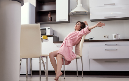 bathrobes: Pretty woman stretching herself in morning on kitchen Stock Photo