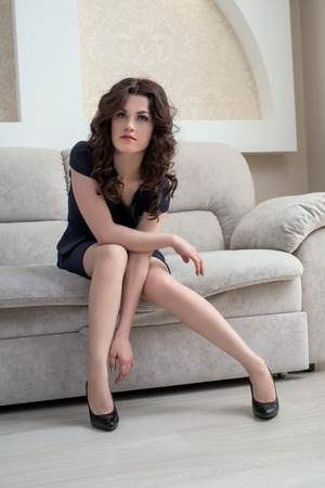 brunette girl: Image of stylish brunette sitting on couch in hotel room