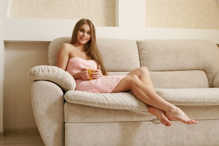 attractive couch: Lovely young woman resting in living room after shower