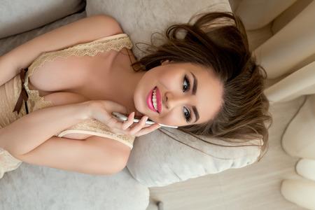 mujer desnuda: Vista superior del modelo atractivo que habla por el teléfono mientras está acostado en el sofá