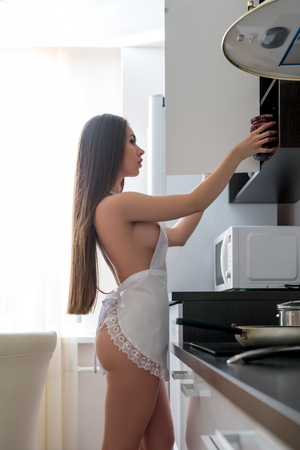 nude babe: Image of nude housewife in apron puts jam into cupboard