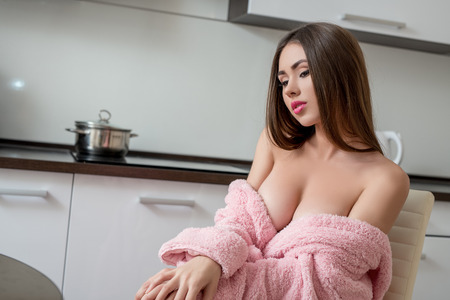 beautiful naked woman: Image of pretty busty girl posing in pink bathrobe on kitchen Stock Photo