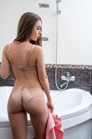 Bathroom. Back view of sexy brunette dressed in erotic lingerie