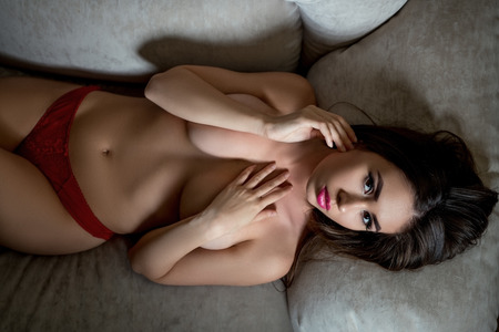 Top view of topless busty brunette posing at camera while lying on sofa