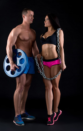 black man: Image of bodybuilder and athletic girl looking at each other