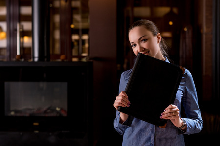 Image of smiling waitress hiding her face behind menu