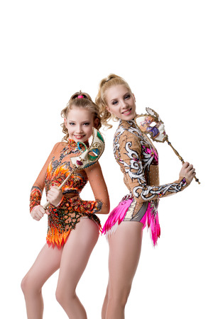 gymnastics equipment: Pretty young gymnasts posing with carnival masks. Isolated on white background Stock Photo