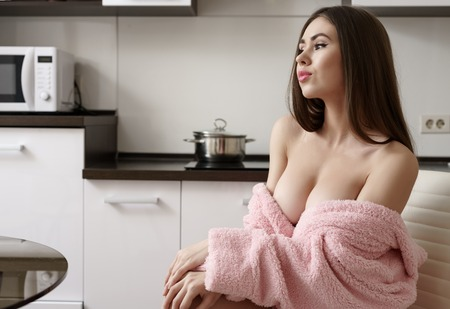 nude brunette: Image of seductive busty woman posing on kitchen in morning Stock Photo