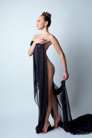 nudo integrale: Nudità ed eleganza. modella nuda in posa con un panno in studio Archivio Fotografico