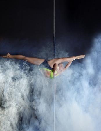 pas: Image of flexible pole dancer performs acrobatic pas Stock Photo
