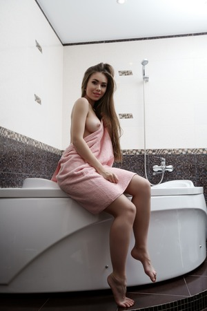 nude babe: Seductive woman bares her breast while sitting on bath