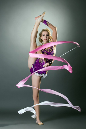 young gymnast: Studio image of rhythmic gymnast performs with ribbon Stock Photo