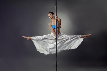 harmonous: Image of flexible pretty girl dancing on pole in studio