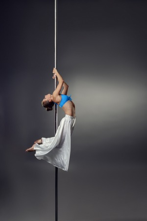 go go dancer: Image of petite woman dancing on pylon in studio