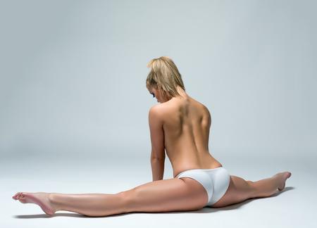 Vista posterior de la mujer en topless que hace fractura de gimnasia en el estudio Foto de archivo
