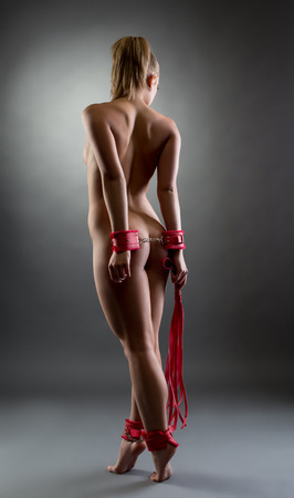 nude adult: Studio photo of naked girl handcuffed hands and feet
