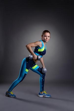 Aptitud. Linda chica ejercicio con pesas, sobre fondo gris