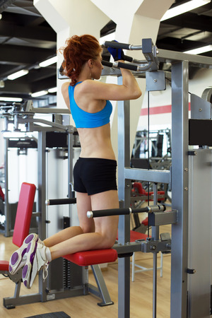 simulator: View of young redhead girl exercising on simulator in gym Stock Photo