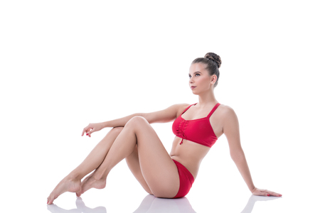 slender woman: Charming gymnast sitting, pulling her knees to chest