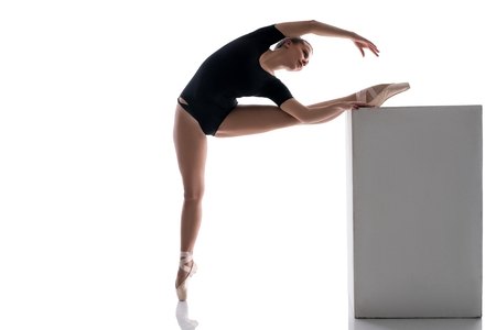 bodysuit: Studio image of ballerina putting her leg on cube while warming up