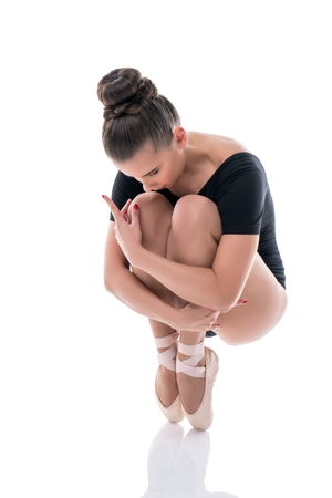 pointes: Ballerina posing on pointes, clutching her knees to chest