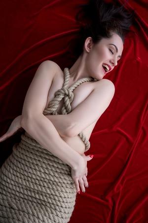 mujer sexy desnuda: Shibari. Imagen de la mujer contenta atado con cuerda de yute
