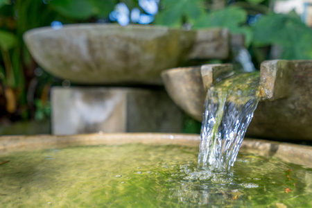 Tropical garden. Image of stone bowl with water flowing. Thailand