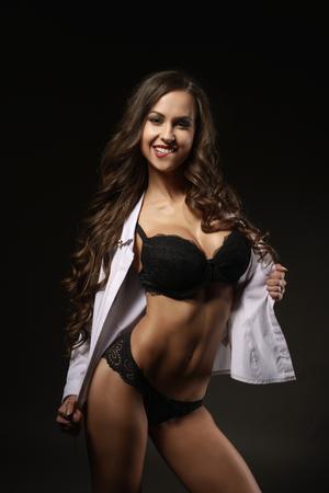 mujeres eroticas: Sexy chica con una sonrisa coqueta en ropa interior negro y una camisa blanca desabrochada posando en el estudio.