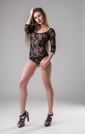junge nackte mädchen: Studio Foto von sexy langbeinigen Modell in der Spitze Bodysuit in die Kamera posiert