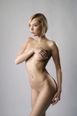 mujeres desnudas: Foto del estudio de rubia desnuda con corte de pelo bob, sobre fondo gris