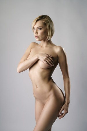 naked woman: Studio photo of nude blonde with bob haircut, on gray background