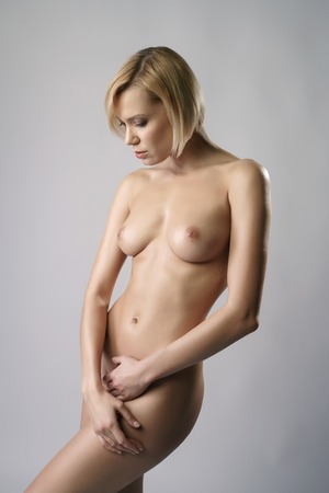 sexy woman nude: Studio image of nude blonde with perfect body, on gray backdrop Stock Photo