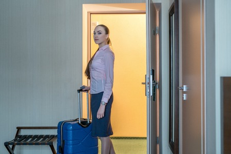 entered: Hotel. Beautiful woman with luggage entered into room Stock Photo