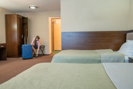shoes off: Image of beautiful woman takes off her shoes in hotel room