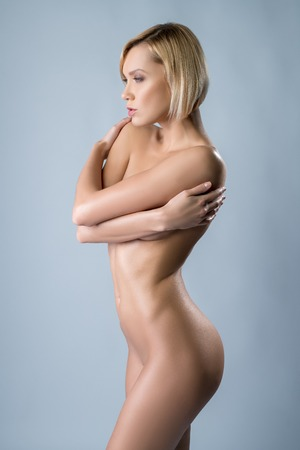 sexy nude women: Studio photo of naked woman with perfect body hugging herself
