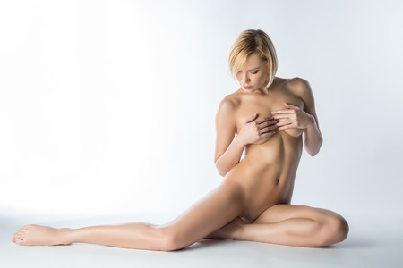 Studio photo of sensual naked blonde posing covering her breasts