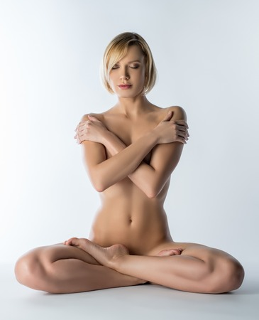 sexy topless woman: Naked blonde meditates while sitting in lotus position