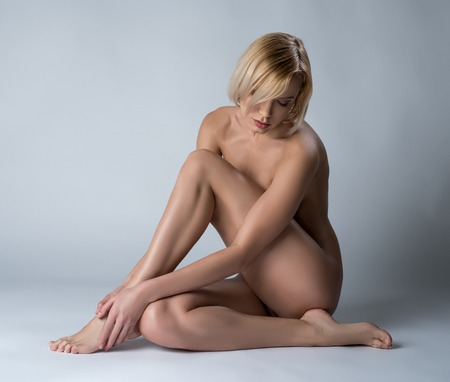 female nudity: Image of sexy nude blonde sitting with her head bowed
