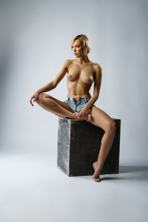 beautiful naked woman: Sexy blonde with naked breasts posing sitting on cube Stock Photo