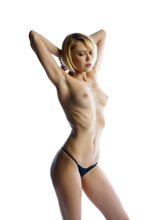 Topless blonde posing with her hands behind head. Isolated on white backdrop Stock Photo