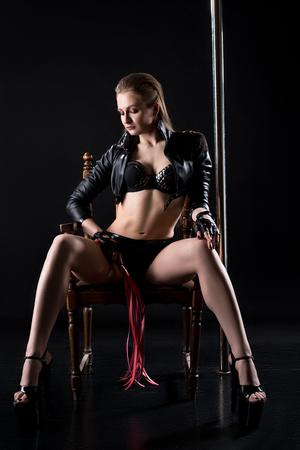 femmes nues sexy: femme dominatrice sexy avec le fouet à la main est assis sur une chaise