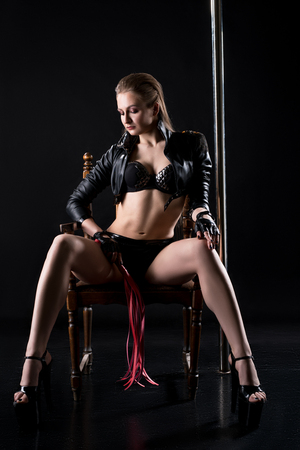 erotic woman: Sexy domineering woman with whip in her hand sits on chair Stock Photo