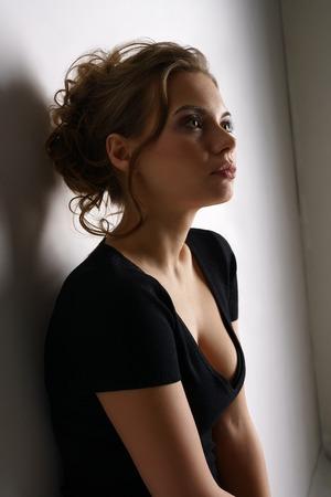 neckline: Studio portrait of beautiful girl wearing black casual dress Stock Photo