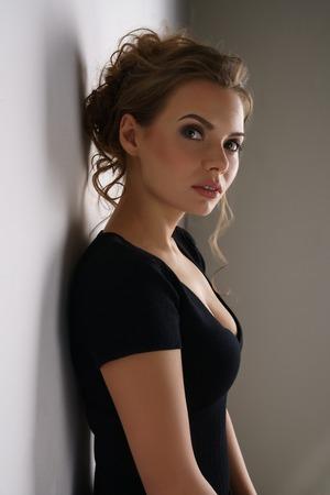 Studio fotografico di giovane e bella bruna in abito nero casual