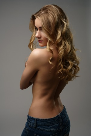 Rear view on topless fair-haired model posing at camera Stock Photo