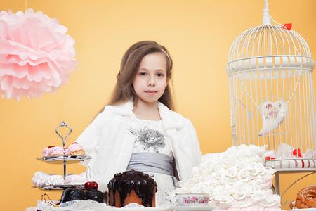 sweet treats: Lovely girl posing with sweet treats in studio, on yellow background Stock Photo