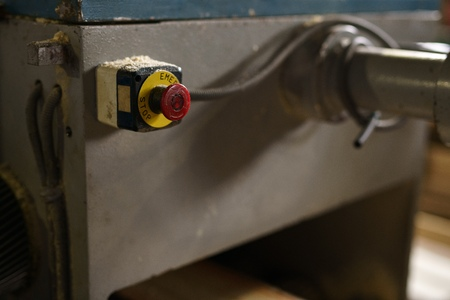 sawmill: At sawmill. Image of stop button on machine, close-up