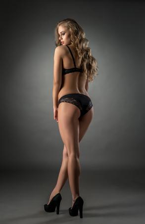mujer rubia desnuda: Imagen de la mujer sensual en ropa interior que presenta de nuevo a la cámara