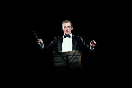 Studio photo of male music conductor holding his baton